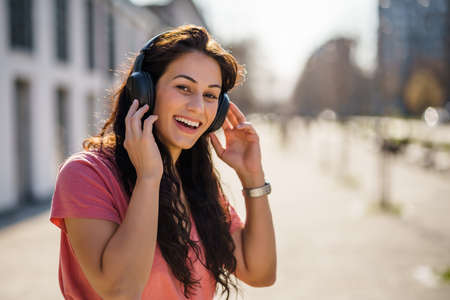 Happy young woman is enjoying sunny day outdoor in city.