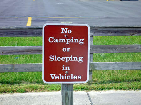 Sign near small airport prohibiting camping or sleeping in vehicles.