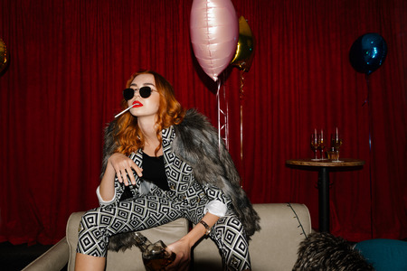 Posh attractive redhead woman drinking whiskey at a party