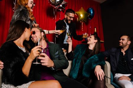 백그라운드에서 토스트하는 사람들과 파티에서 키스 커플 스톡 콘텐츠
