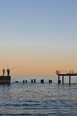 Sundown on sea. Three fishermans on pier.