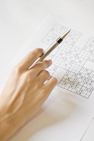 A hand holding a mechanical pen on a sudoku grid.