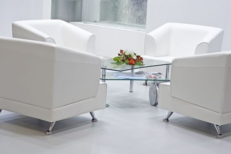 Four white armchairs with glass table