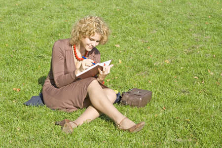 Business women with notebook sits on grass