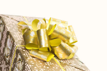 detail of a gift box with golden ribbon and bow