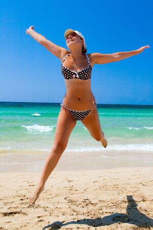 Young women jump on sea beach Stock Photo
