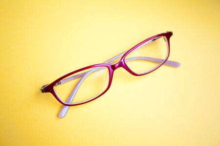 Fashion glasses on yellow background