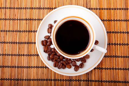 coffee cup with beans on bamboo rug photo