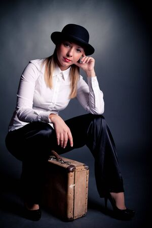 studio shot of gangster styled women sit on suitcase