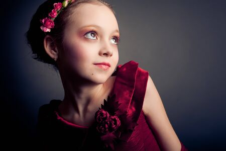 Young model in red dress posing on black background