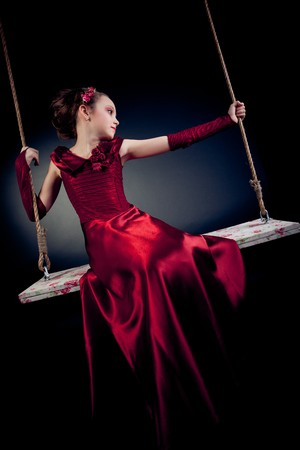 Young model in red dress on swing on black background