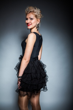 beautiful women in black dress posing on dark background