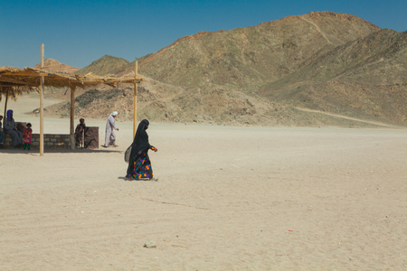 bedouin: bedouin woman in black burqa walking in the desert Stock Photo
