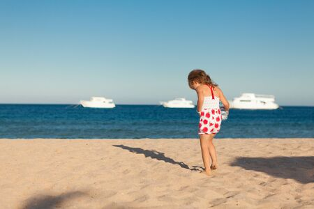 little colours: pretty little young girl searching in yellow sea sand