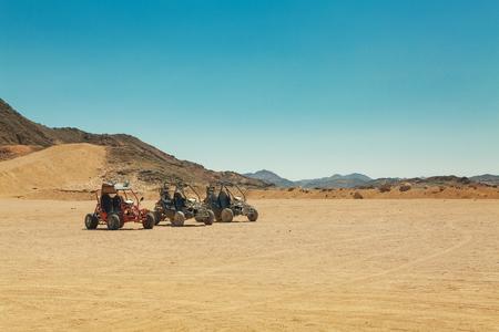 atv: three atv standing in hot desert under clear sky
