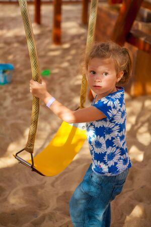 Beautiful little girl on a swing Stock Photo