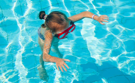 Little girl learns to swim underwater in mask