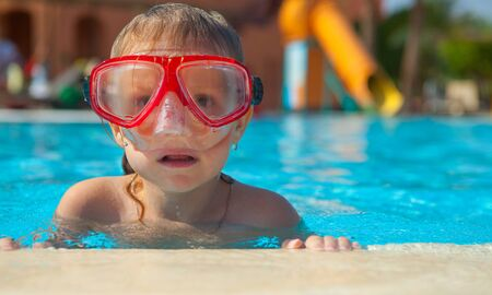 Little girl in a mask for diving on the edge of the pool
