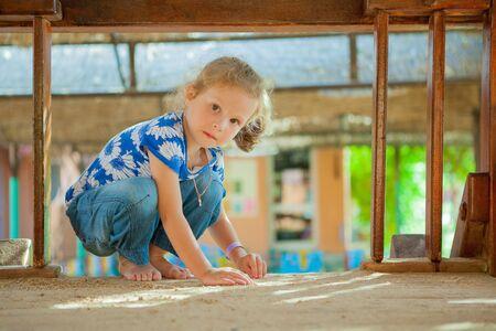 sandbox: The beautiful girl playing to a sandbox
