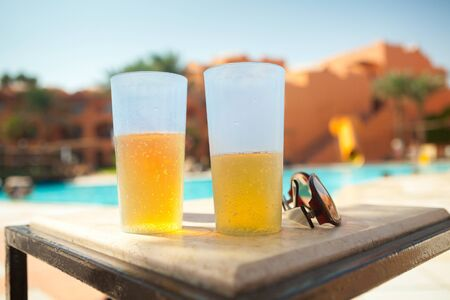 two glass of beer and sunglasses on pool background Stock Photo