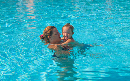 Mother teaches daughter to swim Stock Photo