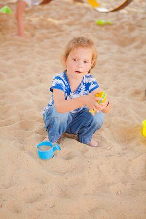 The beautiful girl playing to a sandbox