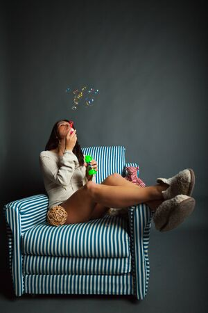 young woman in stripped armchair with flying soap bubbles Stock Photo