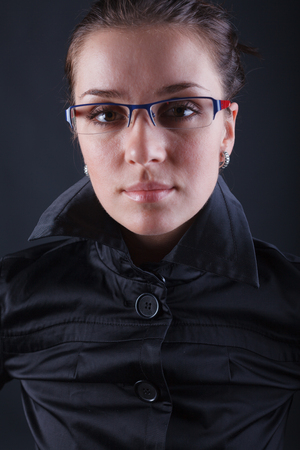 business woman in glasses on dark background