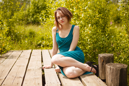 Young beautiful girl in blue dress sitting on wooden pierce