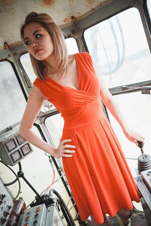 Young asian woman in red dress posing in excavator cabin