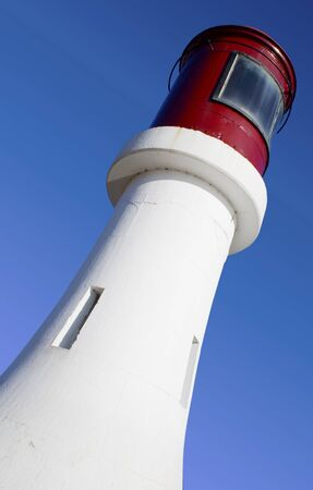 contrasting: Lighthouse painted brillian white with contrasting red top set against vivid blue sky
