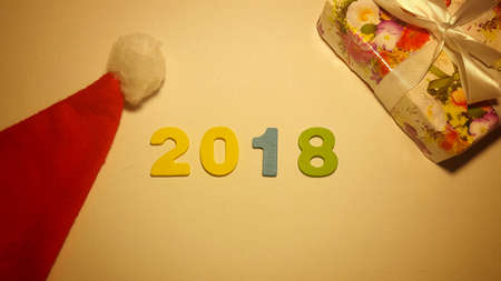 Colored figures to form the number 2018 on white canvas with Christmas gifts Stockfoto