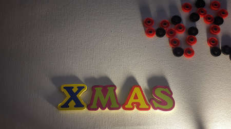 Colored letters spell out Xmas on white canvas with Christmas gifts.