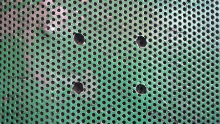green metal texture with holes. Background with holes. Stockfoto