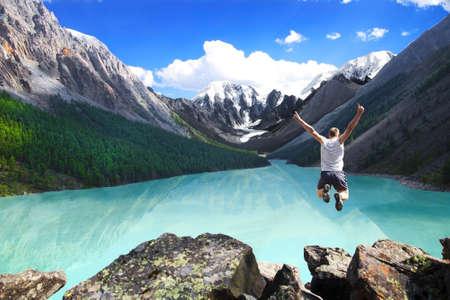 美しい山の風景、湖と人間の跳躍