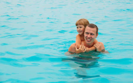 The happy child swimming with the father in the tropical resort in the sea. Concept of summer vacations. 版權商用圖片