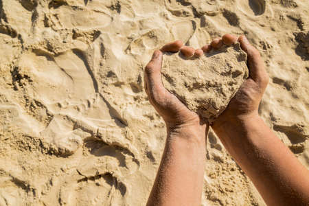Heart from sand, a symbol in a hand. Conceptual design.