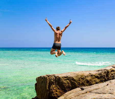 The happy young man jumping in the sea