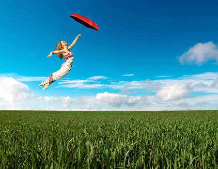 Flying girl with red umbrella in the blue sky over a green field photo