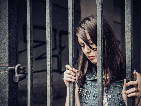 Junge Frau, die im Gefängnis sitzt Standard-Bild