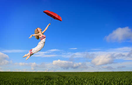 Beautiful young woman flying on a green meadow with a red umbrella photo
