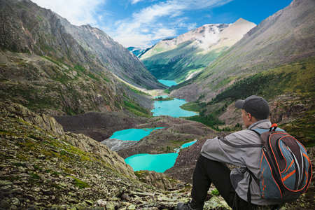 Hiker with backpack sitting on top of the mountain and enjoying view of the valley with mountain lakes photo