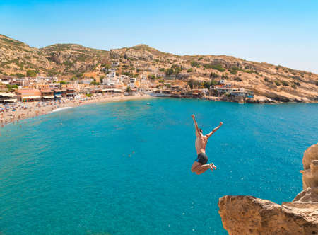 cliff jumping: Extreme sports. Young man jumping from the cliff in the sea. Stock Photo