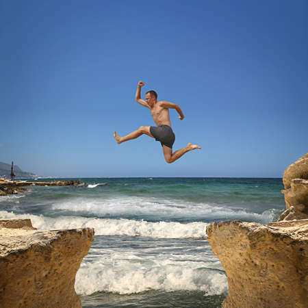 Man jumping over the abyss between two rocky mountains. Extreme sports , risk, success. photo