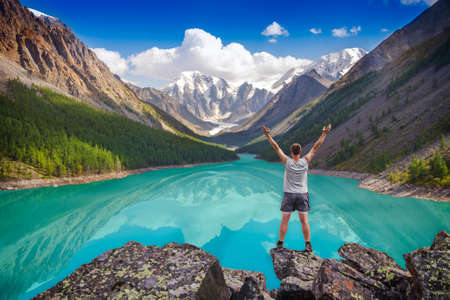 Young hiker standing with raised hands near the beautiful mountain lake and enjoying valley view. Concept of extreme sport and active life. photo