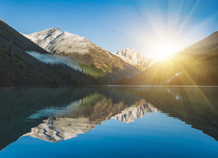 mirror on the water: Sunrise and mountains reflected in the water