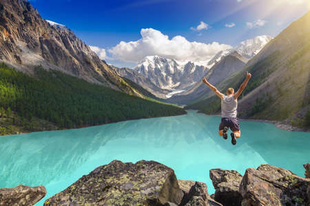 man outdoors: Beautiful mountain landscape with lake and jumping man