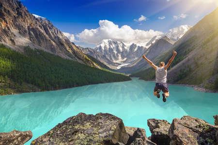 Bella montagna paesaggio con lago e uomo che salta