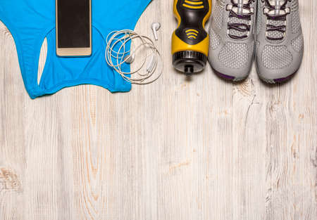 sports clothing: Sport shoes and water bottle with sports equipment on wooden floor.