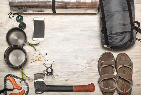 wood burner: Overhead view of hiking gear laid out for a trip on a rustic wood floor. Gear include, compass, phone, tent, ax, gas, burner, matches, shoes. Stock Photo